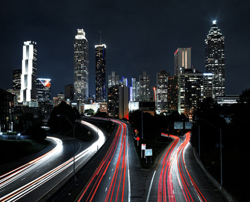 City by night with cars as a stream of red light