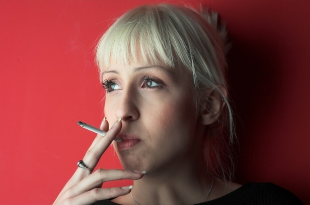 Woman leaning against red background smoking a cigarette