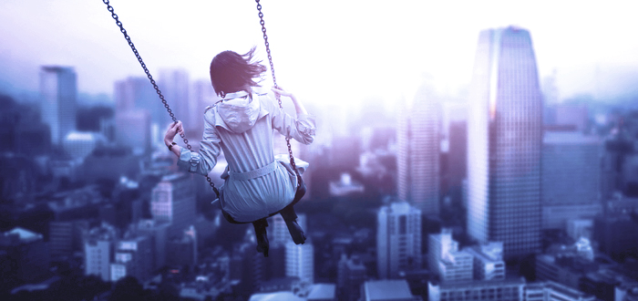 Woman on swing with view of skyscapers